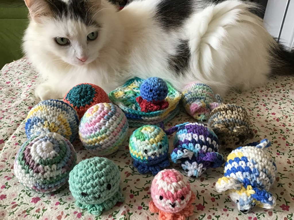Kitty cat showing off a bunch of crochet kitty toys